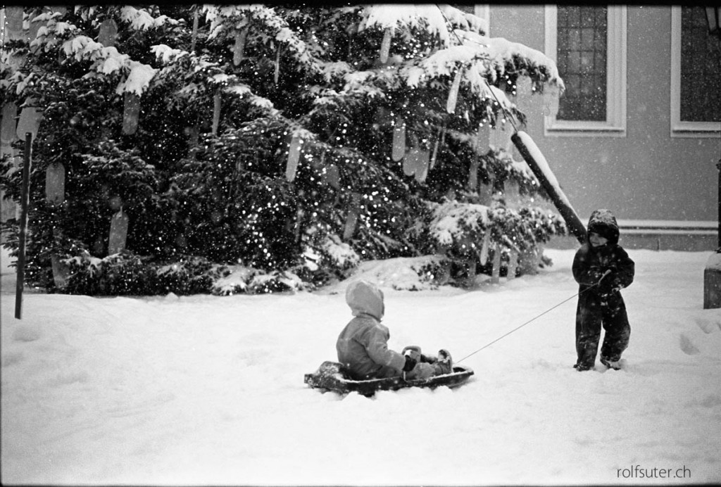 Two kids with a sled at the christmas tree in St. Gallen