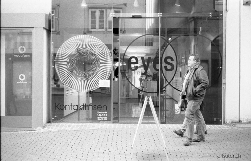 Man walking along a shop display window with big circles.