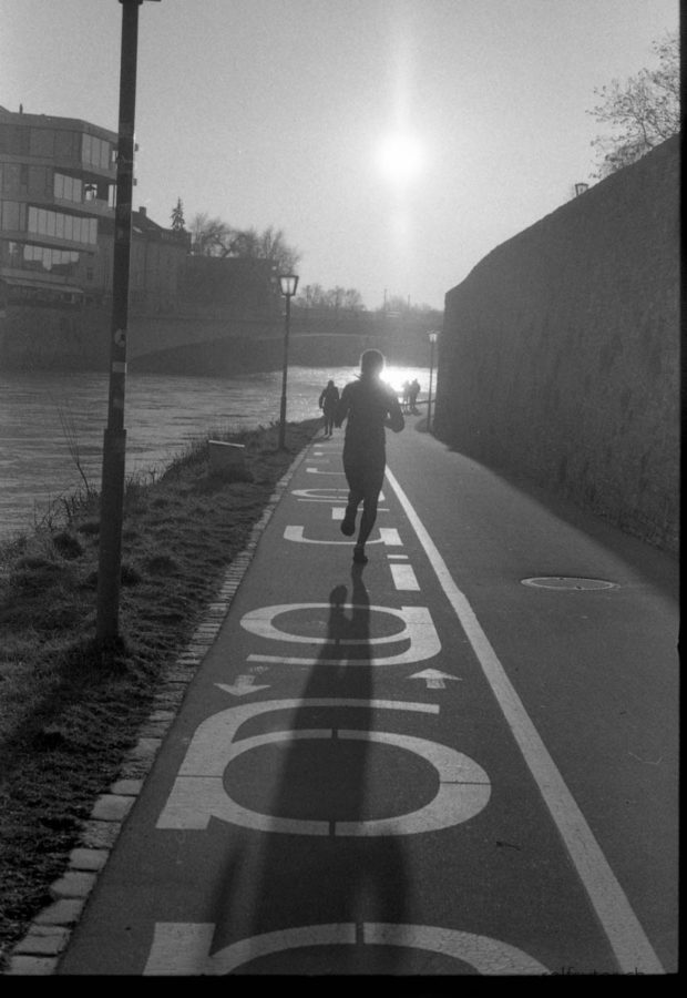Woman jogging along a way with big letters towards against the light.